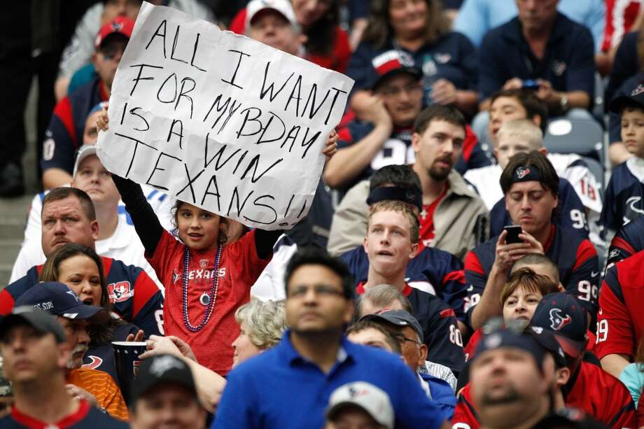 A Texans fan holds up a sign wishing for a win for her birthday during the third quarter. (Brett Coomer / Houston Chronicle)