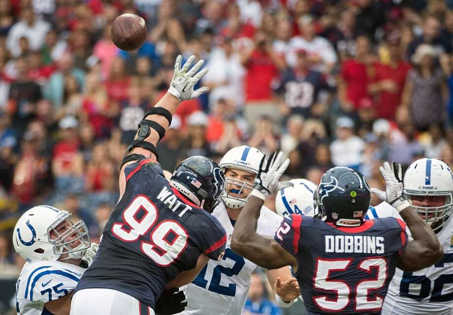 Colts quarterback Andrew Luck (12) gets off a pass as Texans defensive end J.J. Watt (99) and linebacker Tim Dobbins (52) apply pressure. (Smiley N. Pool / Houston Chronicle)