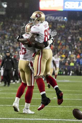 49ers wide receiver Delanie Walker, left, gets a hug from wide receiver Vernon Davis after scoring a second quarter touchdown against the Patriots in their game at Gillette Stadium on Dec. 16, 2012. Photo: Kelvin Ma, Special To The Chronicle