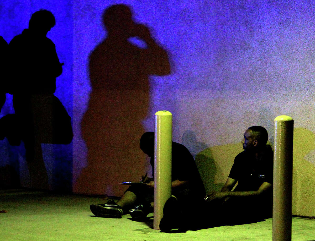 Police question men near the Mayan Theater after an incident late Sunday, Dec. 16, 2012.