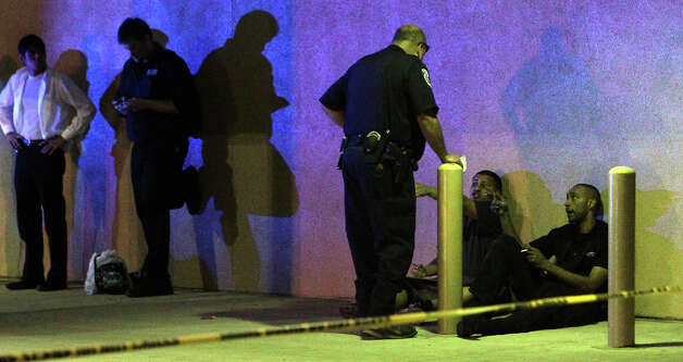 Police question a man near the Mayan Theater after an incident late Sunday, Dec. 16, 2012. Photo: JOHN DAVENPORT, San Antonio Express-News / SAN ANTONIO EXPRESS-NEWS
