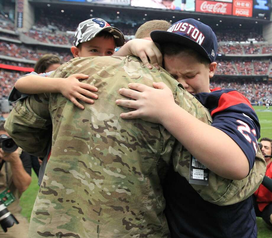Army Chief Warrant Officer Eric Spoerle hugs his sons, Tristin, 12, right, and Brandon, 6. (Karen Warren / Chronicle)