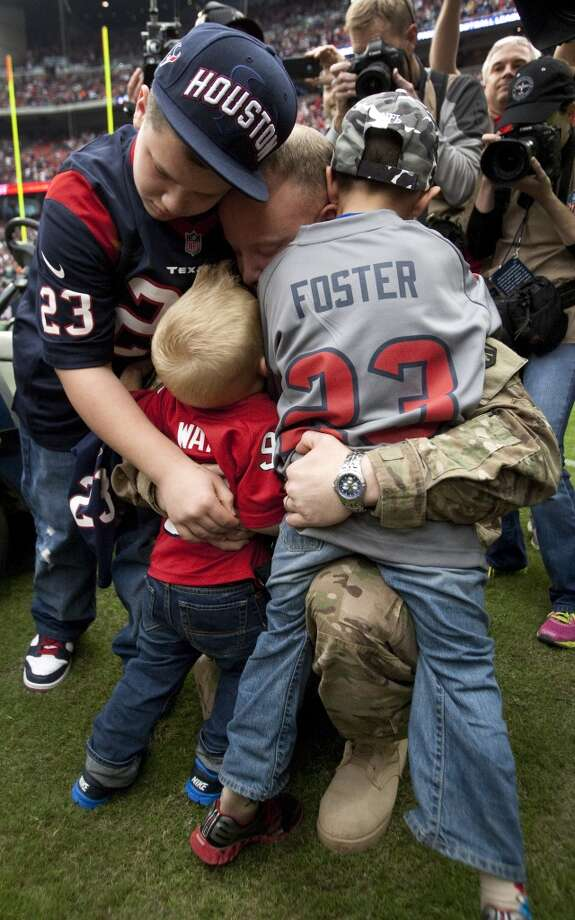 Army Chief Warrant Officer Eric Spoerle embraces his children Tristin, Brandon and Eric, Jr. (Brett Coomer / Chronicle)