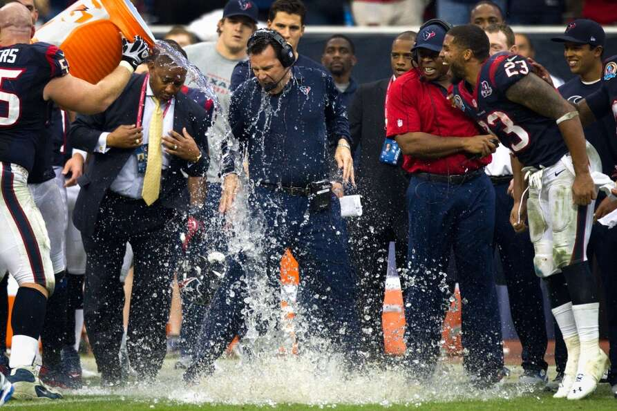 Houston Texans head coach Gary Kubiak is doused with a bucket of water at the end the Texans victory