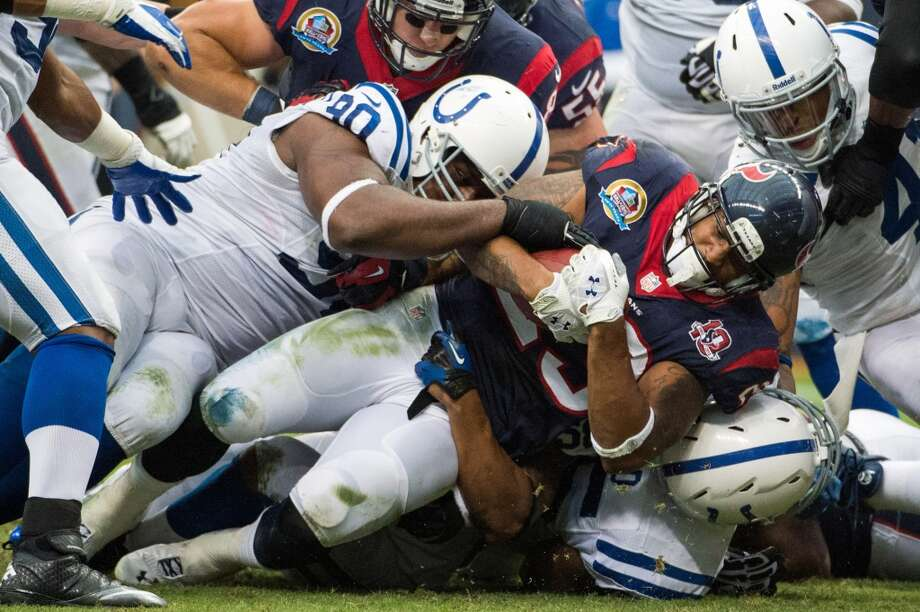 Texans running back Arian Foster (23) is brought down by Colts defensive end Cory Redding (90) as he goes off tackle for a two-yard gain inside the Colts red zone during the first quarter. (Smiley N. Pool / Houston Chronicle)