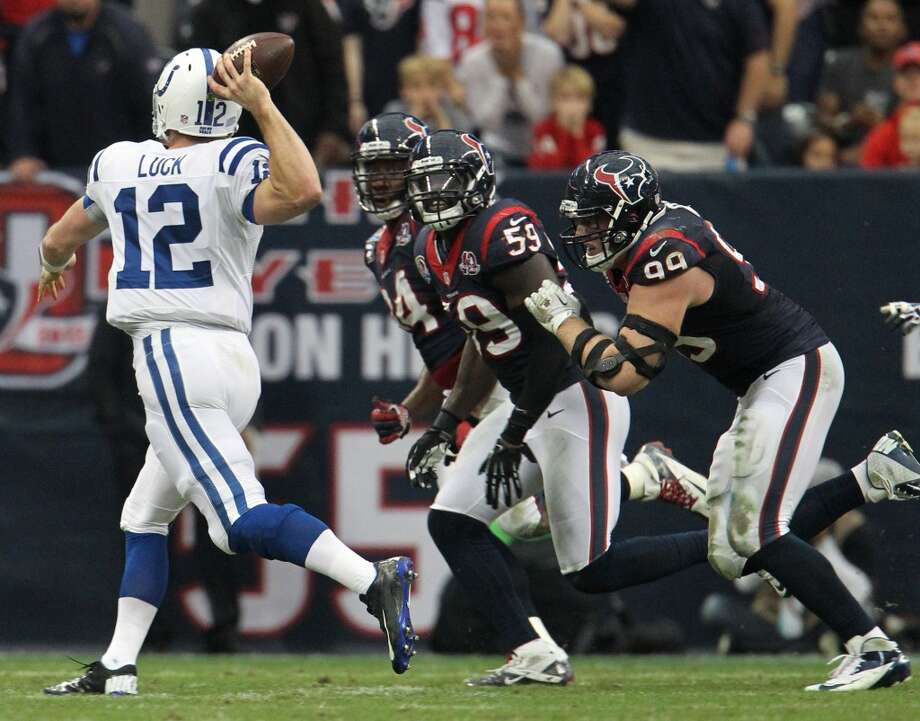 Colts quarterback Andrew Luck (12) throws on the run as Houston Texans defensive end J.J. Watt (99), outside linebacker Whitney Mercilus (59) and defensive end Antonio Smith (94) provide pressure during the second quarter. (Karen Warren / Houston Chronicle)