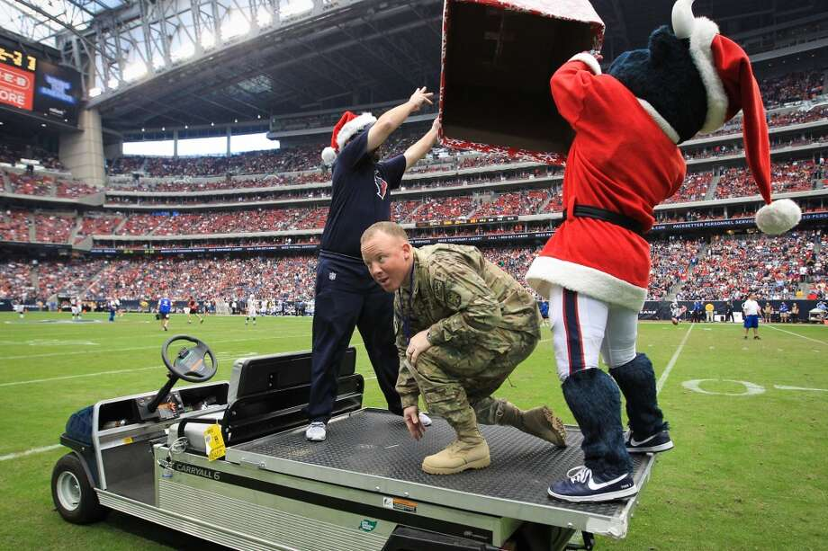 Army Chief Warrant Officer Eric Spoerle pops out of a Christmas present as he surprises his children during halftime. (Karen Warren / Houston Chronicle)
