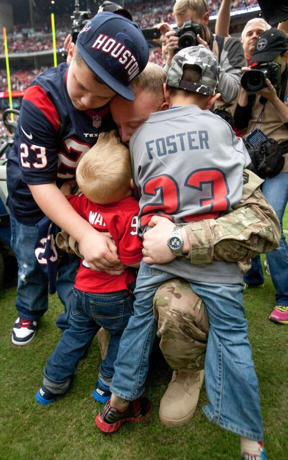 Army Chief Warrant Officer Eric Spoerle embraces his childrenTristin, Brandon and Eric, Jr., after he surprised them at halftime. Spoerle had returned from Afghanistan. (Brett Coomer / Houston Chronicle)