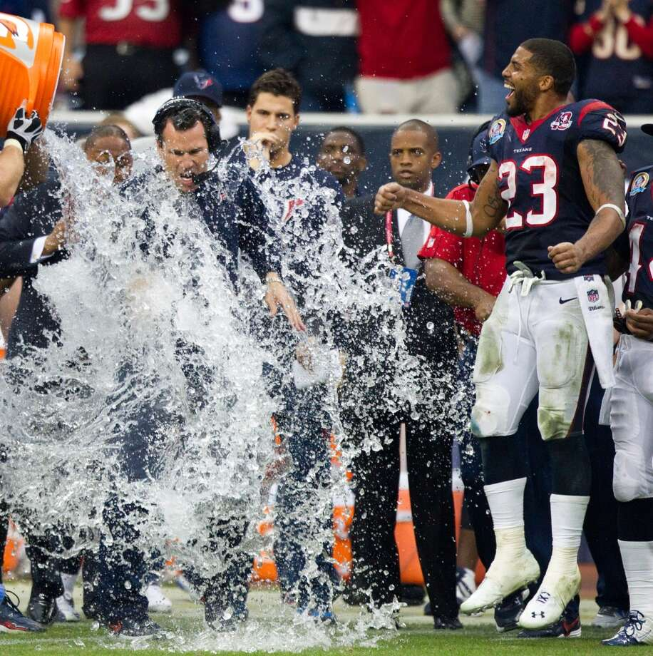 Texans head coach Gary Kubiak is doused with a bucket of water at the end of the fourth quarter as running back Arian Foster (23) celebrates. (Brett Coomer / Houston Chronicle)