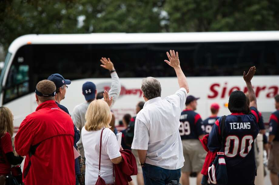 Texans fans wave as the Colts team buses depart the stadium after the Texans 29-17 victory. (Smiley N. Pool / Houston Chronicle)