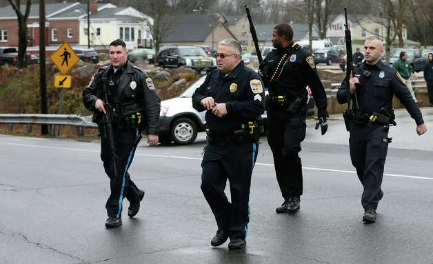 Police officers cross the road after searching a strip mall near an elementary school, which was in a lockdown, in Ridgefield, Conn., Monday, Dec. 17, 2012, after a suspicious person was seen near a train station close by. On Friday, authorities say a gunman killed his mother at their home and then opened fire inside the Sandy Hook Elementary School in Newtown, killing 26 people, including 20 children, before taking his own life. Photo: AP