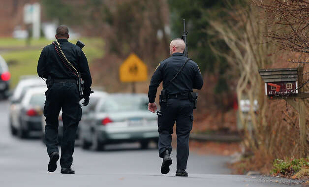 Police officers walk up to an elementary school, which was in a lockdown, in Ridgefield, Conn., Monday, Dec. 17, 2012, after a suspicious person was seen near the train station close to the school. On Friday, authorities say a gunman killed his mother at their home and then opened fire inside the Sandy Hook Elementary School in Newtown, killing 26 people, including 20 children, before taking his own life. Photo: AP