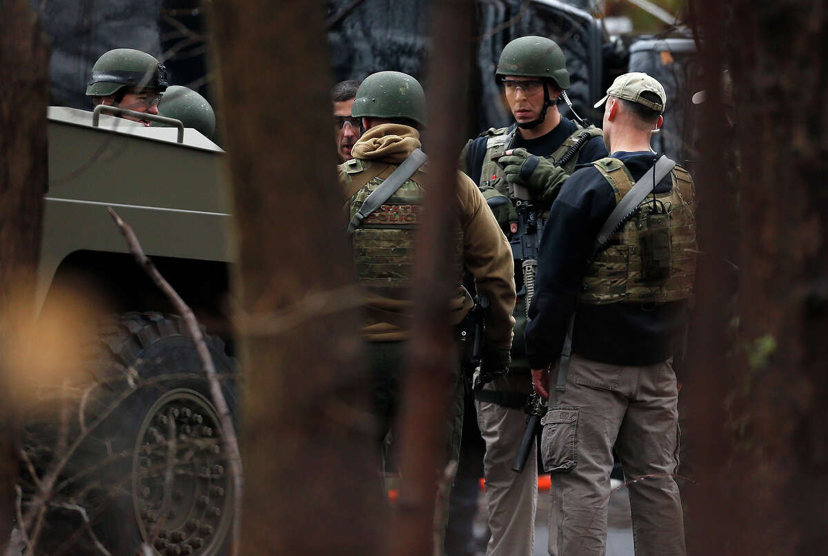 A Connecticut State Police tactical team gathers while searching near an elementary school, which was in a lockdown, in Ridgefield, Conn., Monday, Dec. 17, 2012, after a suspicious person was seen near a nearby train station. On Friday, authorities say a gunman killed his mother at their home and then opened fire inside the Sandy Hook Elementary School in Newtown, killing 26 people, including 20 children, before taking his own life.