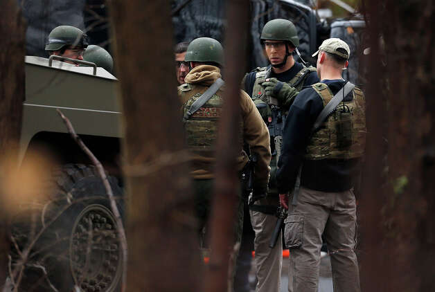 A Connecticut State Police tactical team gathers while searching near an elementary school, which was in a lockdown, in Ridgefield, Conn., Monday, Dec. 17, 2012, after a suspicious person was seen near a nearby train station. On Friday, authorities say a gunman killed his mother at their home and then opened fire inside the Sandy Hook Elementary School in Newtown, killing 26 people, including 20 children, before taking his own life. Photo: AP