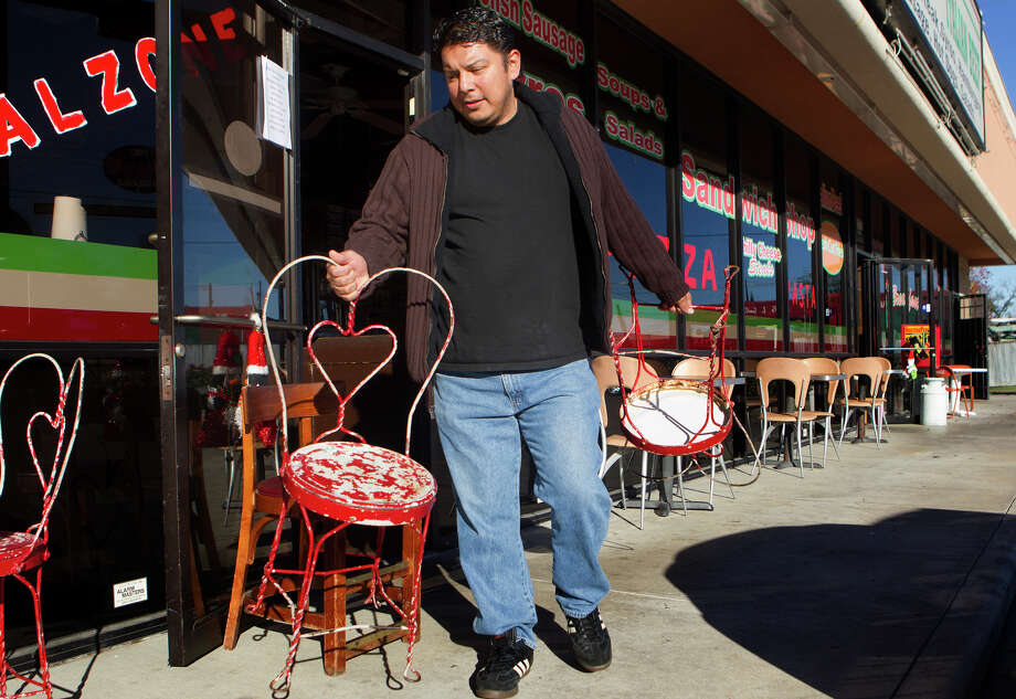 "Chicago Pizza and Italian Beef cashier Frank Perez prepares the outdoor seating on Airline Drive, Monday, Dec. 17, 2012, in Houston. Perez said that last week when the weather was cold, people don't sit outside. ""When the weather is nicer, we have more walk-in customers and people that sit outside,"" Perez said. ""When the weather is more cold, we get more deliveries."" Photo: Cody Duty, Houston Chronicle / © 2012 Houston Chronicle"