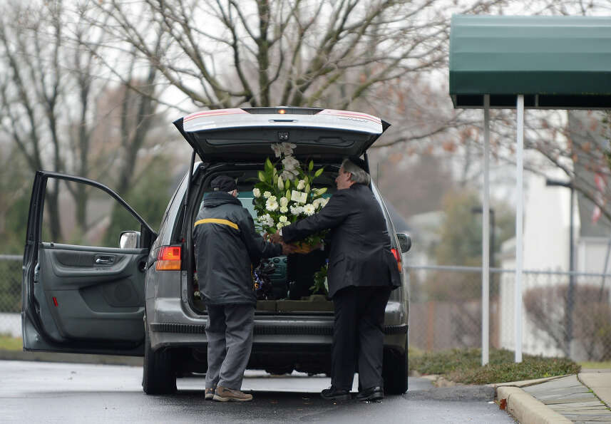 A florist delivers funeral bouquets for Noah Pozner's funeral December 17, 2012 at the Abraham L. Gr
