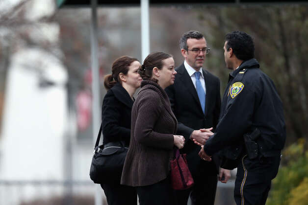 FAIRFIELD, CT - DECEMBER 17:  People greet a police officer as they arrive for the funeral services of six year-old Noah Pozner, who was  killed in the shooting massacre in Newtown, CT, at Abraham L. Green and Son Funeral Home on December 17, 2012 in Fairfield, Connecticut. Today is the first day of funerals for some of the twenty children and seven adults who were killed by 20-year-old Adam Lanza on December 14, 2012. Photo: Spencer Platt, Getty Images / 2012 Getty Images