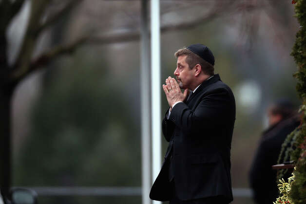 FAIRFIELD, CT - DECEMBER 17:  A man gestures with his hands as people arrive for the funeral services of six year-old Noah Pozner, who was  killed in the shooting massacre in Newtown, CT, at Abraham L. Green and Son Funeral Home on December 17, 2012 in Fairfield, Connecticut. Today is the first day of funerals for some of the twenty children and seven adults who were killed by 20-year-old Adam Lanza on December 14, 2012. Photo: Spencer Platt, Getty Images / 2012 Getty Images