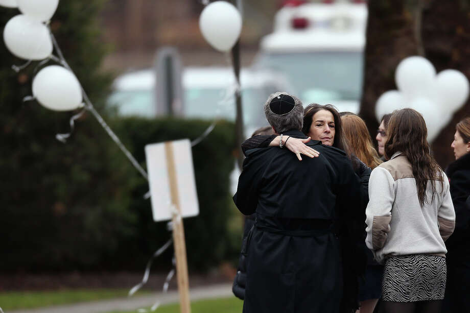 FAIRFIELD, CT - DECEMBER 17:  People embrace as they arrive for the funeral services of six year-old Noah Pozner, who was  killed in the shooting massacre in Newtown, CT, at Abraham L. Green and Son Funeral Home on December 17, 2012 in Fairfield, Connecticut. Today is the first day of funerals for some of the twenty children and seven adults who were killed by 20-year-old Adam Lanza on December 14, 2012. Photo: Spencer Platt, Getty Images / 2012 Getty Images
