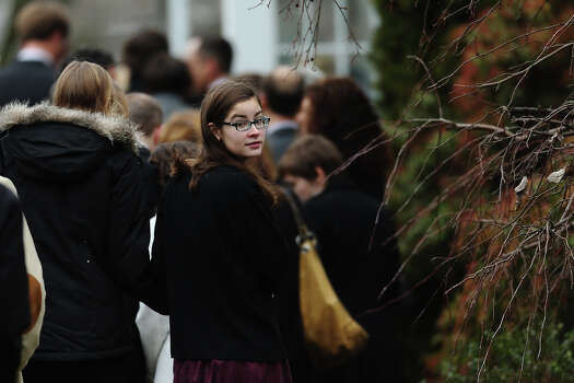 FAIRFIELD, CT - DECEMBER 17:  A woman looks back as she arrives for the funeral services of six year-old Noah Pozner, who was  killed in the shooting massacre in Newtown, CT, at Abraham L. Green and Son Funeral Home on December 17, 2012 in Fairfield, Connecticut. Today is the first day of funerals for some of the twenty children and seven adults who were killed by 20-year-old Adam Lanza on December 14, 2012. Photo: Spencer Platt, Getty Images / 2012 Getty Images