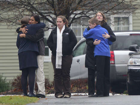 Mourners embrace December 17, 2012 at the funeral for Jack Pinto, 6, one of the victims of the December 14, Sandy Hook elementary school shooting, in Newtown, Connecticut.  Funerals began Monday in the little Connecticut town of Newtown after the school massacre that took the lives of 20 small children and six staff, triggering new momentum for a change to America's gun culture. Photo: EMMANUEL DUNAND, AFP/Getty Images / 2012 AFP
