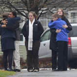 Mourners embrace December 17, 2012 at the funeral for Jack Pinto, 6, one of the victims of the December 14, Sandy Hook elementary school shooting, in Newtown, Connecticut.  Funerals began Monday in the little Connecticut town of Newtown after the school massacre that took the lives of 20 small children and six staff, triggering new momentum for a change to America's gun culture.