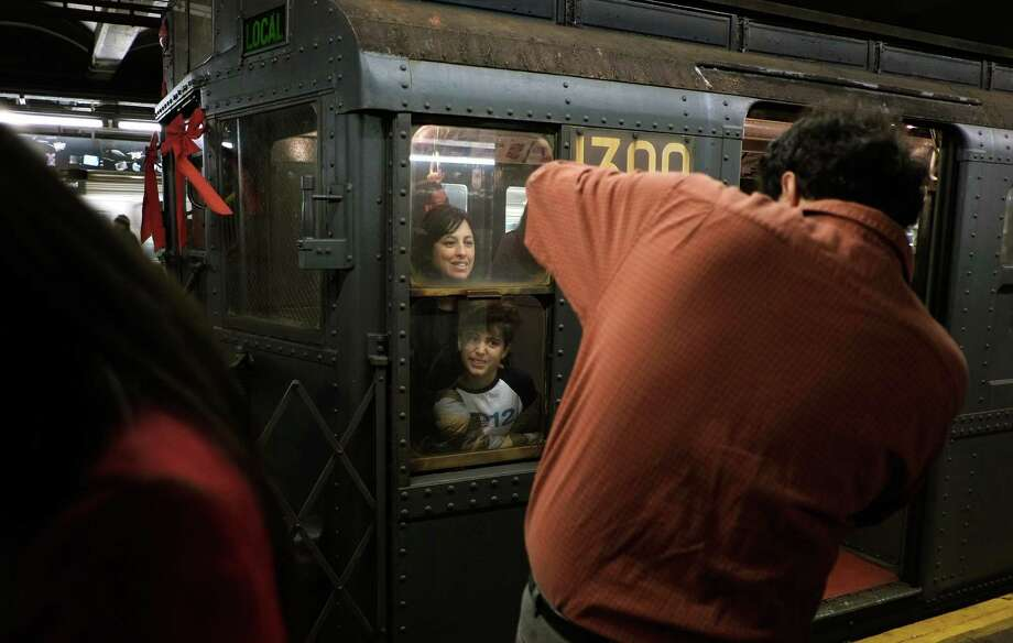 NEW YORK, NY - DECEMBER 16:  People get their picture taken in the window of a vintage R9 New York City subway on December 16, 2012 in New York City. The New York Metropolitan Transportation Authority (MTA) runs vintage subway trains from the 1930's-1970's each Sunday along the M train route from Manhattan to Queens through the first of the year. Photo: Preston Rescigno, Getty Images / 2012 Getty Images