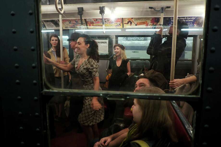 NEW YORK, NY - DECEMBER 16:  People dance to live music in a vintage New York City subway car as it sits in the 2nd Ave. station on December 16, 2012 in New York City. The New York Metropolitan Transportation Authority (MTA) runs vintage subway trains from the 1930's-1970's each Sunday along the M train route from Manhattan to Queens through the first of the year. Photo: Preston Rescigno, Getty Images / 2012 Getty Images
