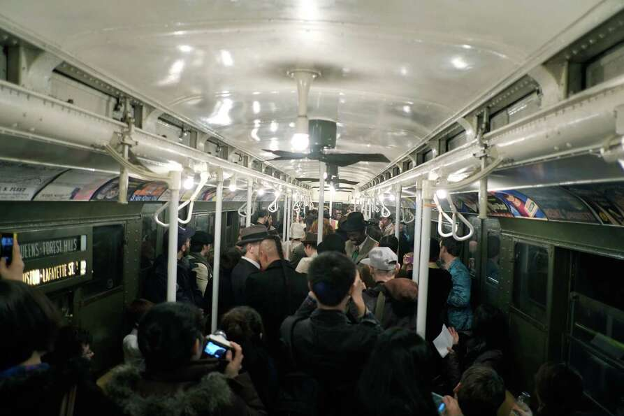 NEW YORK, NY - DECEMBER 16:  People crowd into a vintage New York City subway car as people dance to