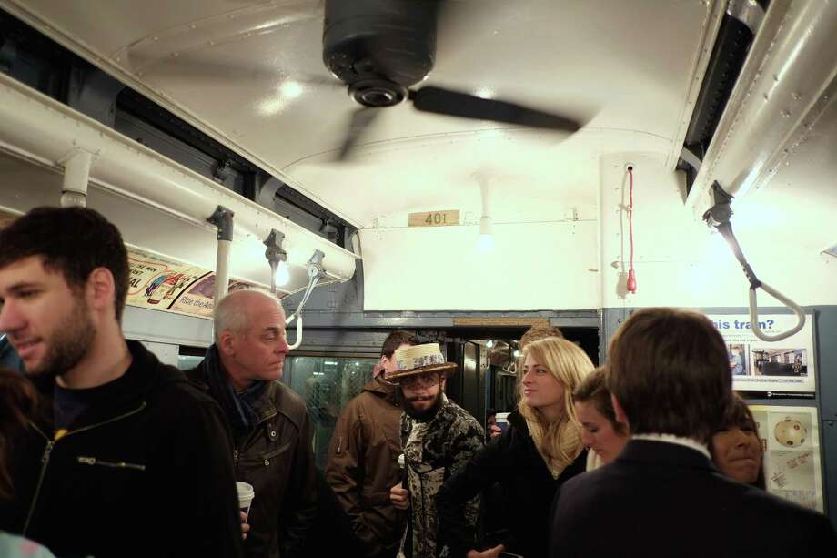NEW YORK, NY - DECEMBER 16:  People walk through a vintage New York City subway car as it moves along the M line on December 16, 2012 in New York City. The New York Metropolitan Transportation Authority (MTA) runs vintage subway trains from the 1930's-1970's each Sunday along the M train route from Manhattan to Queens through the first of the year. Photo: Preston Rescigno, Getty Images / 2012 Getty Images