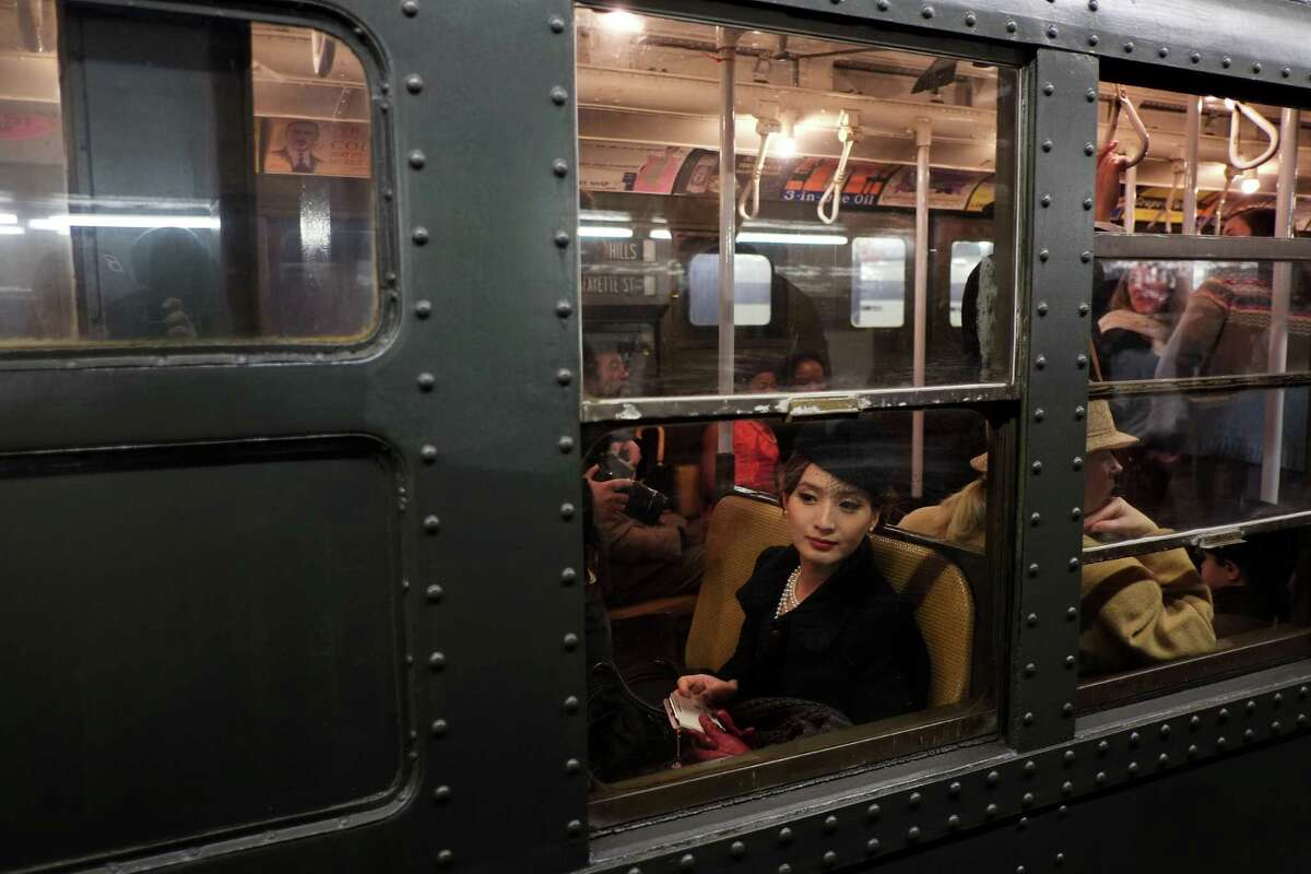 NEW YORK, NY - DECEMBER 16: A woman dressed in period costume sits in a vintage New York City subway on December 16, 2012 in New York City. The New York Metropolitan Transportation Authority (MTA) runs vintage subway trains from the 1930's-1970's each Sunday along the M train route from Manhattan to Queens through the first of the year.