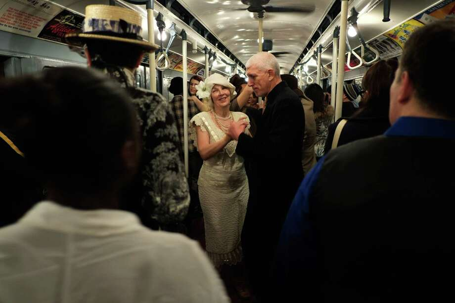 NEW YORK, NY - DECEMBER 16:  People dance in a vintage New York City subway car as it moves along the M line on December 16, 2012 in New York City. The New York Metropolitan Transportation Authority (MTA) runs vintage subway trains from the 1930's-1970's each Sunday along the M train route from Manhattan to Queens through the first of the year. Photo: Preston Rescigno, Getty Images / 2012 Getty Images