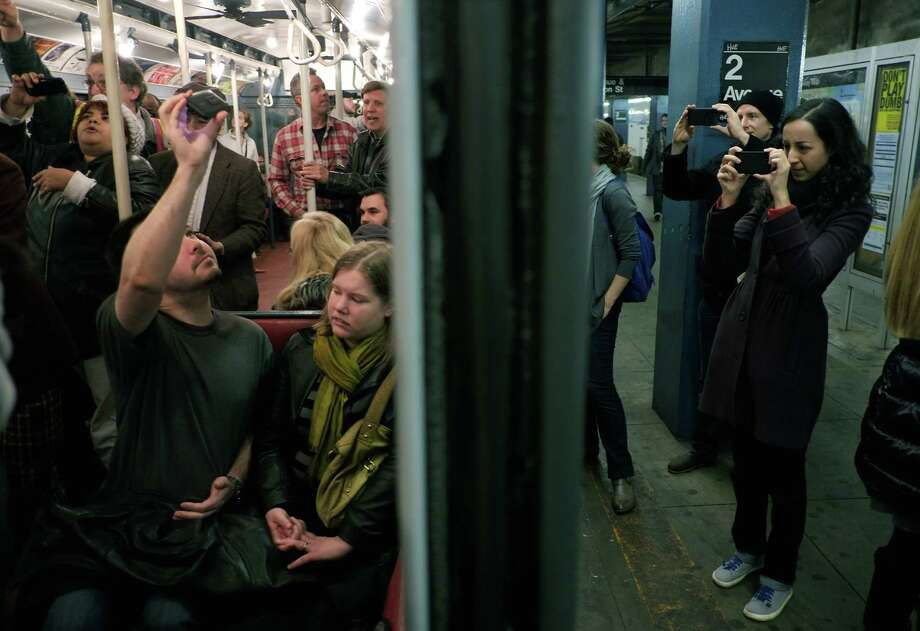NEW YORK, NY - DECEMBER 16:  People take pictures of a vintage New York City subway car as it sits in the 2nd Ave. station on December 16, 2012 in New York City. The New York Metropolitan Transportation Authority (MTA) runs vintage subway trains from the 1930's-1970's each Sunday along the M train route from Manhattan to Queens through the first of the year. Photo: Preston Rescigno, Getty Images / 2012 Getty Images