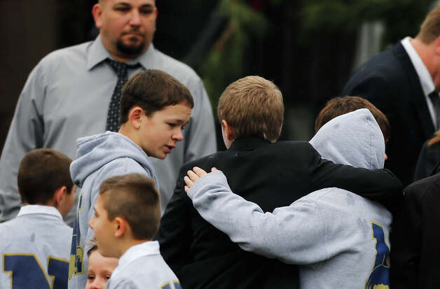 Studens embrace while wearing Newtown school shirts outside the funeral for six-year-old student shooting victim Jack Pinto in Newtown, Conn., Monday, Dec. 17, 2012. A gunman opened fire at Sandy Hook Elementary School in the town on Friday, killing 26 people, including 20 children before killing himself. Photo: AP