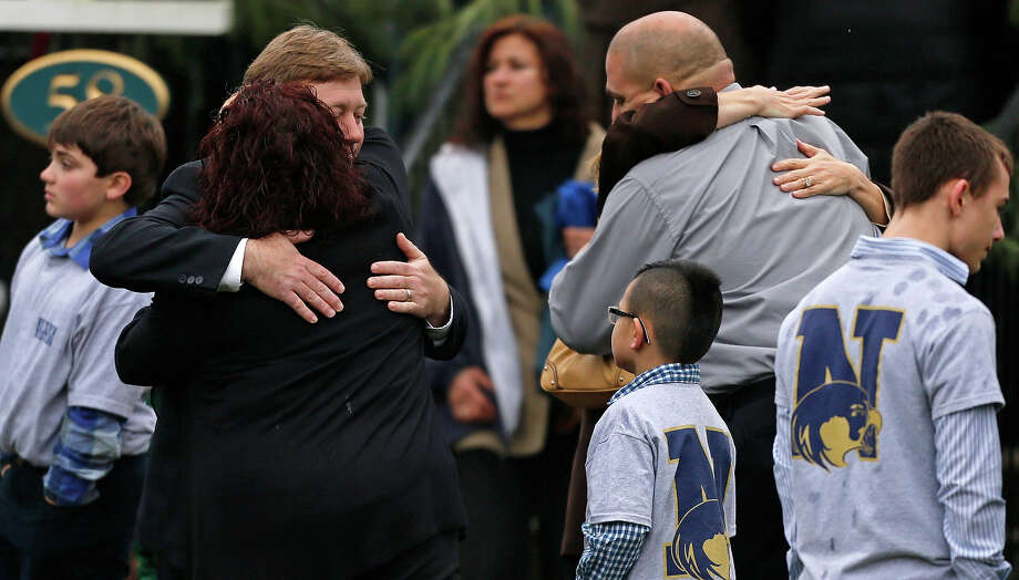 Families embrace while surrounded by children wearing Newtown school shirts outside the funeral for six-year-old shooting victim Jack Pinto in Newtown, Conn., Monday, Dec. 17, 2012. A gunman opened fire at Sandy Hook Elementary School in the town on Friday, killing 26 people, including 20 children before killing himself. Photo: AP