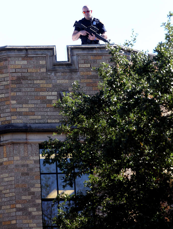 A police officer with a rifle stands on the roof of Cambridge Elementary School during a lockdown situation Monday December 17, 2012. Photo: JOHN DAVENPORT, San Antonio Express-News / ©San Antonio Express-News/Photo Can Be Sold to the Public