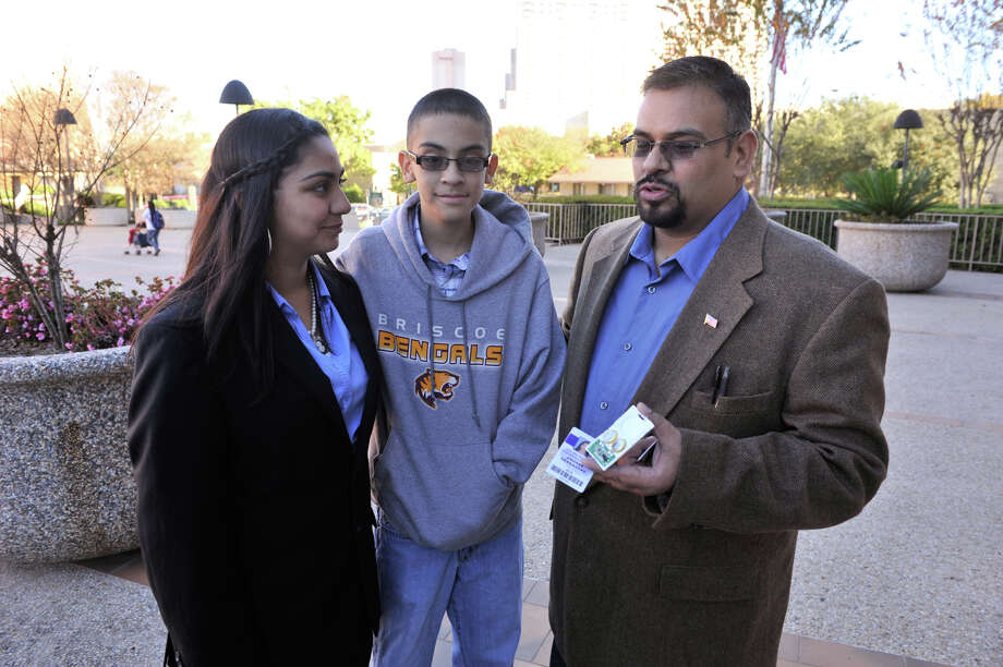 Steven Hernandez (right) the father of NISD student Andrea Hernandez (left), along with son Vinson, 13, shows off the RFID equiped student ID in front of the San Antonio Federal Courthouse prior to a hearing Monday morning. Hernandez is fighting NISD to get a chip-less badge for his daughter. Photo: Robin Jerstad/For The Express-Ne
