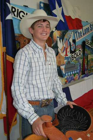 Cody Teel stands in front of the Texas flag at Kountze High School, displaying his state champion saddke abd belt buckle trophies. Photo: Rachael Hartman/HCN