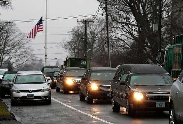 A hearse and family limousines for six-year-old shooting victim Jack Pinto rolls past a flag at half staff as the funeral procession heads through the historic district in Newtown, Conn., Monday, Dec. 17, 2012. A gunman opened fire on Friday at Sandy Hook Elementary School in the town, killing 26 people, including 20 children before killing himself. Photo: AP