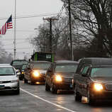 A hearse and family limousines for six-year-old shooting victim Jack Pinto rolls past a flag at half staff as the funeral procession heads through the historic district in Newtown, Conn., Monday, Dec. 17, 2012. A gunman opened fire on Friday at Sandy Hook Elementary School in the town, killing 26 people, including 20 children before killing himself.