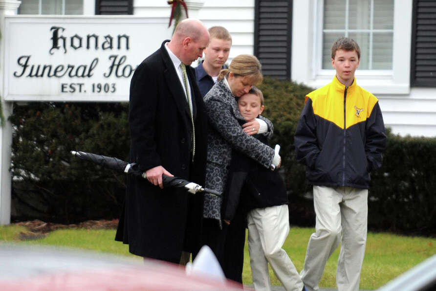 A family leaves the Honan Funeral Home, in Newtown, Conn., following the funeral of Jack Pinto, 6, o