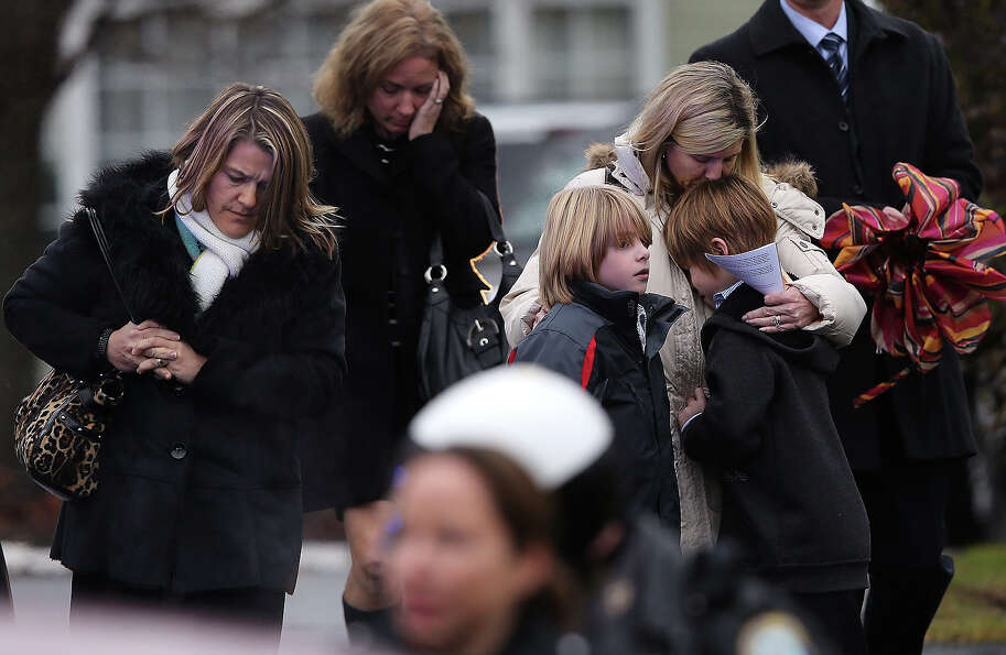 NEWTOWN, CT - DECEMBER 17:  A woman comforts a boy as mourners depart Honan Funeral Home after the f