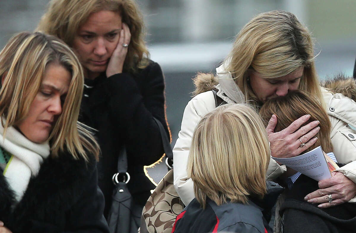 NEWTOWN, CT - DECEMBER 17: A woman comforts a boy as mourners depart Honan Funeral Home after the funeral for 6-year-old Jack Pinto on December 17, 2012 in Newtown Connecticut. Pinto was one of the 20 students killed in the Sandy Hook Elementary School mass shooting.