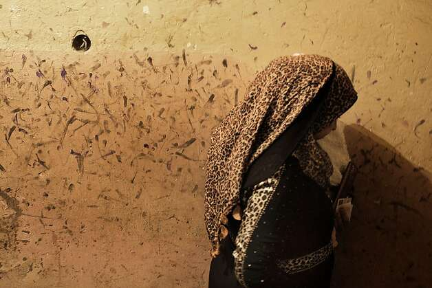 An Egyptian woman walks past a wall stained with ink by voters who tried to clean their marked fingers at a polling station in the historical City of the Dead district in Cairo, on December 15, 2012. Egypt's opposition cried fraud in the first round of a divisive referendum on a new constitution, accusing President Mohamed Morsi's Muslim Brotherhood of rigging votes to adopt the Islamist-backed text.     TOPSHOTS/AFP PHOTO/MARCO LONGARIMARCO LONGARI/AFP/Getty Images Photo: Marco Longari, AFP/Getty Images