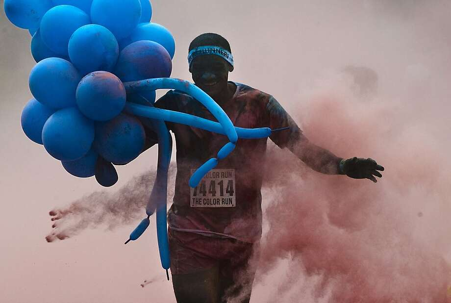 I already feel lighter on my feet:A competitor carrying balloons races in The Color Run 5K event in Rio de Janeiro. The Color Run is more about fun than run. Photo: Antonio Scorza, AFP/Getty Images