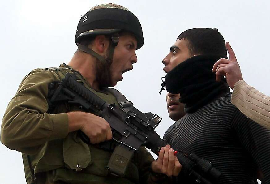 'Occupy' protest: A Palestinian confronts an Israeli soldier in the village of Madama after I