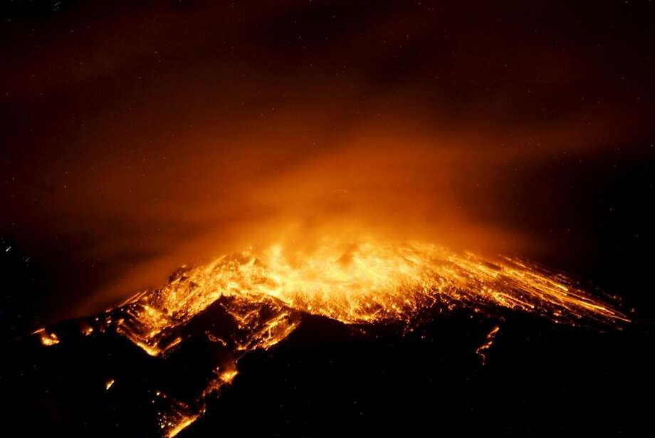 View of an eruption at the Tungurahua volcano, from the city of Banos, early on December 17, 2012. Ecuador issued an orange alert -- the second-highest warning level -- for towns near the Tungurahua volcano on the eve, as its level of activity rose, civil defense officials said. Photo: -, AFP/Getty Images