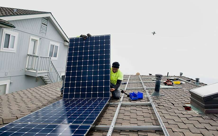 Juan Moedano places a solar panel on a Southern California home. Solar homes get credit for a surplus. Photo: Sam Hodgson, Bloomberg