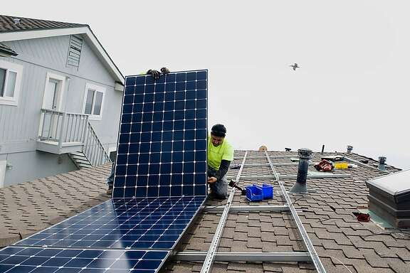 Stellar Solar installers Juan Moedano, right, and Andres Quiroz, unseen, lift a solar panel during installation at a home in Encinitas, California, U.S., on Wednesday, Aug. 15, 2012. Stellar Solar installs residential and commercial solar panels in the San Diego area.