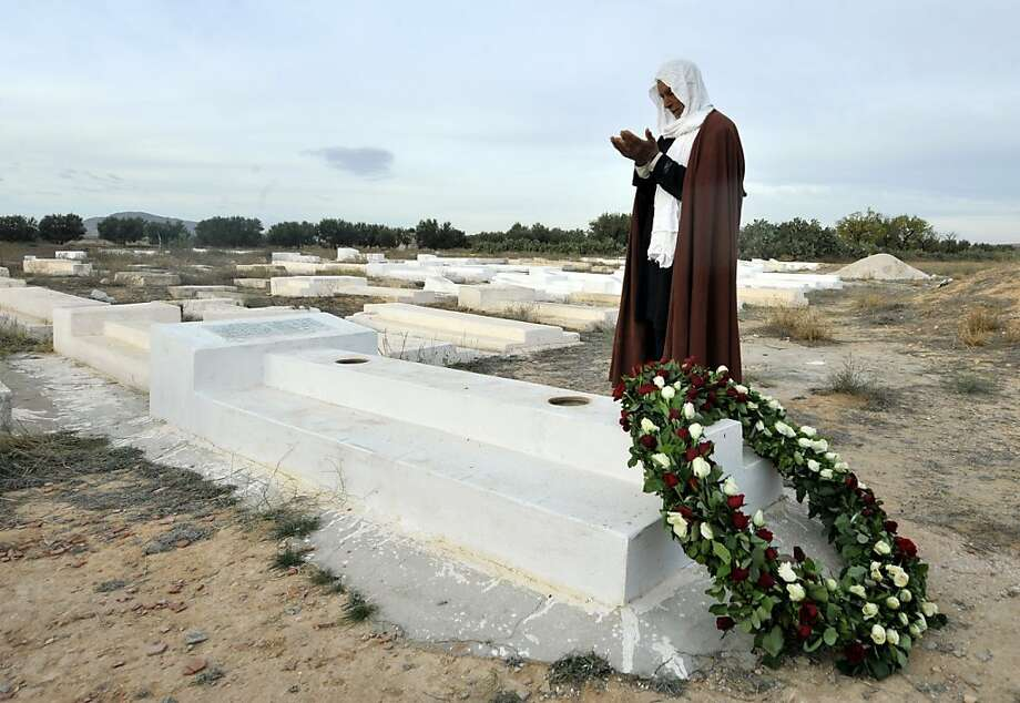 His death gave birth to a movement: A Tunisian man prays at the mausoleum of Mohamed Bouazizi, the young fruit-and-vegetable seller whose self-immolation two years ago kicked off the Arab Spring in the town of Sidi Bouzid. Tunisian President Moncef Marzouki was heckled when he visited the grave earlier in the day. Photo: Fethi Belaid, AFP/Getty Images